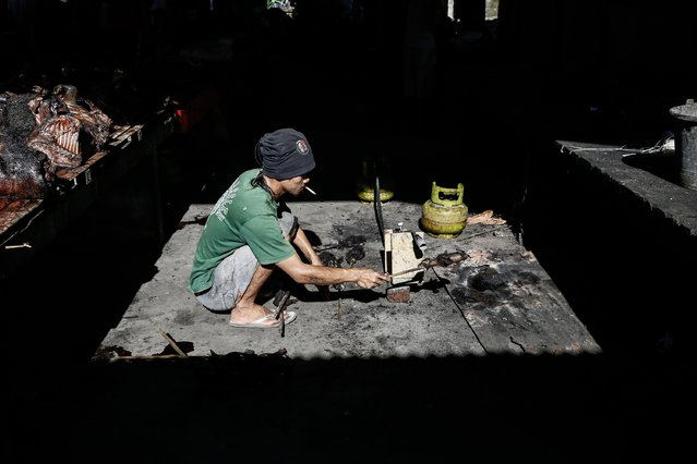 A man roasts a bat at Langowan traditional market on August 9, 2014 in Langowan, North Sulawesi. The Langowan traditional market is famous for selling a variety of extreme food such as dogs, bats, rats, wild boar, and snakes. (Photo by Putu Sayoga/Getty Images)