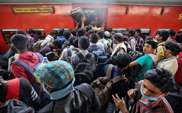 Migrant workers and their families board an overcrowded passenger train, after government imposed restrictions on public gatherings in attempts to prevent spread of coronavirus disease (COVID-19), in Mumbai, India, March 21, 2020. (Photo by Prashant Waydande/Reuters)