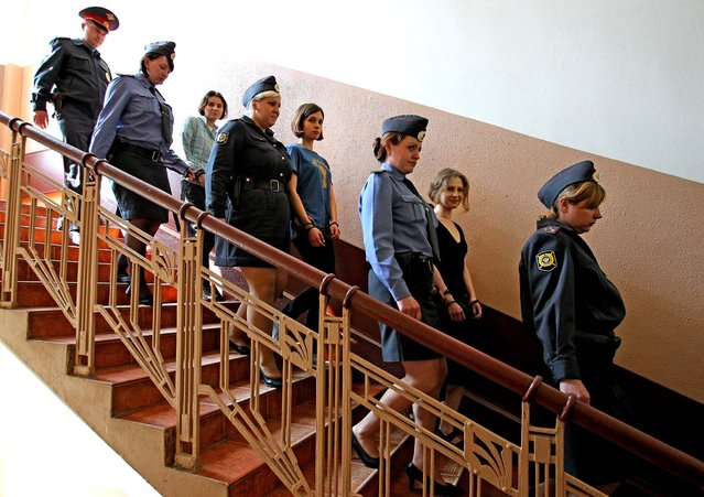 Nadezhda Tolokonnikova (center), Yekaterina Samutsevich (third left), and Maria Alekhina (second right), members of feminist punk group p*ssy Riot are escorted by the police to a court in Moscow. (Photo by Mikhail Metzel/Associated Press)