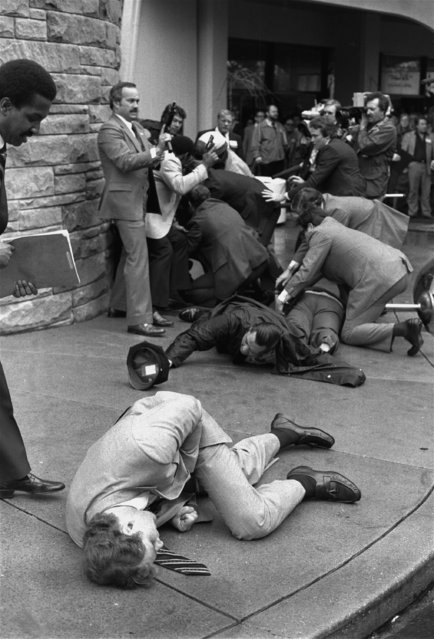 Secret Service agent Timothy J. McCarthy, foreground, Washington policeman, Thomas K. Delehanty, center, and presidential press secretary James Brady, background, lie wounded on a street outside a Washington hotel after shots were fired at U.S. President Reagan on March 30, 1981. (Photo by Ron Edmonds/AP Photo)