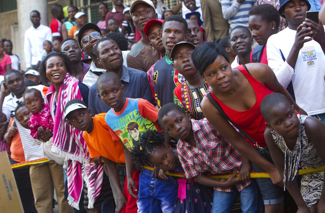 In this picture taken Saturday, September 9, 2017, Zimbabweans follow various performances on the streets of Harare during the International Carnival in the capital. (Photo by Tsvangirayi Mukwazhi/AP Photo)