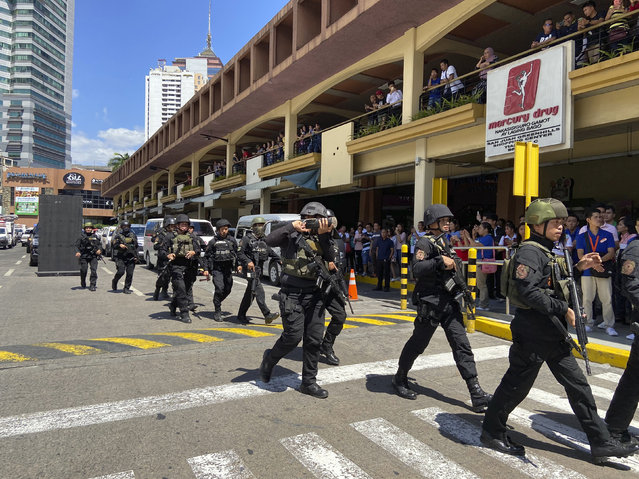 A group of armed police soldiers arrive at the Greenhills Shopping Center Monday, March 2, 2002, in Manila, Philippines. Philippine police on Monday surrounded a shopping mall in an upscale district in the Manila metropolis after gunshots rang out inside and sent shoppers rushing out in panic. (Photo by Aaron Favila/AP Photo)