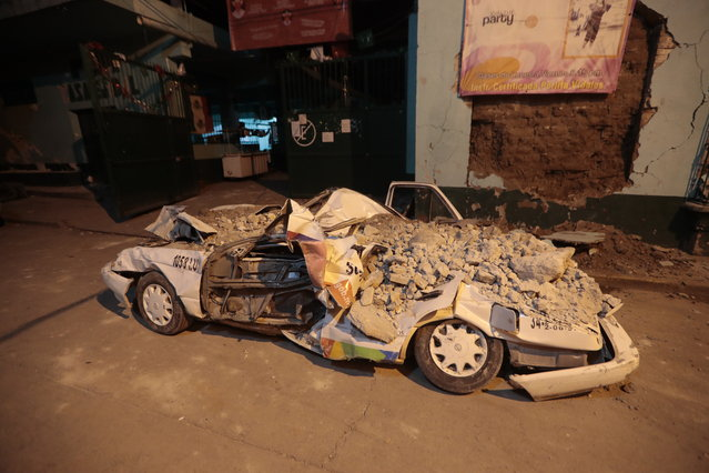 A car stands crushed by rubble after a 7.1 earthquake, in Jojutla, Morelos state, Mexico, Tuesday, September 19, 2017. The earthquake stunned central Mexico, killing more than 100 people as buildings collapsed in plumes of dust. (Photo by Eduardo Verdugo/AP Photo)