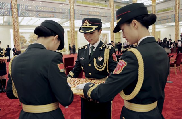 Female soldiers from the honor guards prepare commemorative medals for a ceremony marking the 70th anniversary of the Victory of Chinese People's War of Resistance Against Japanese Aggression, for World War Two veterans, at the Great Hall of the People in Beijing, China September 2, 2015. (Photo by Jason Lee/Reuters)