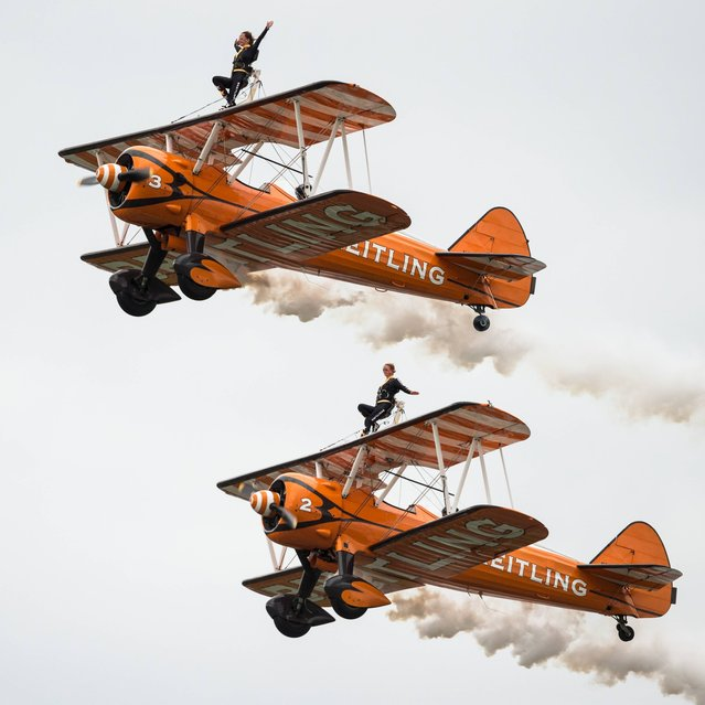 Two Britisch Wingwalkers on biplanes of the Team Breitling  perform during a flight at the AIR14 air show in Payerne, Switzerland, Sunday, August 31, 2014. (Photo by Alessandro della Valle/AP Photo/Keystone)
