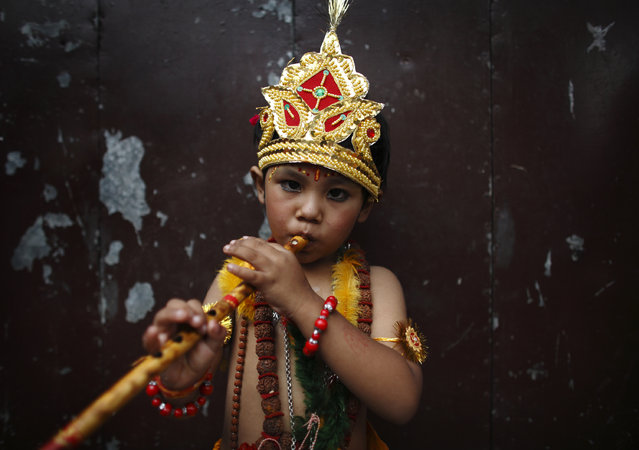 A boy dressed as Lord Krishna blows on a flute as he participates in a parade to mark the Gaijatra Festival in Kathmandu August 3, 2012. (Photo by Navesh Chitrakar/Reuters)