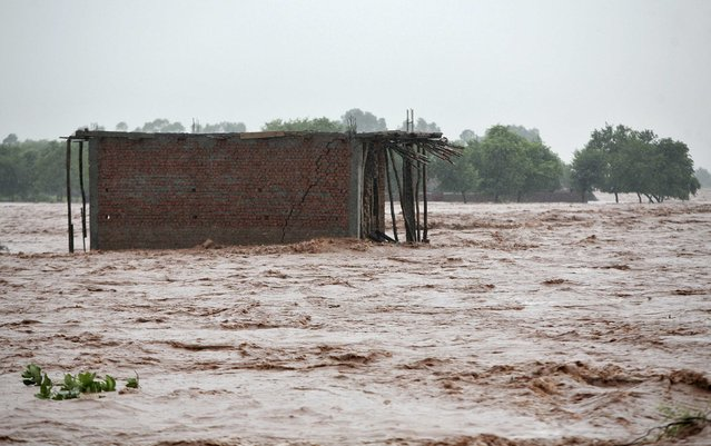 A house under construction is surrounded by the flooded banks of river Tawi after heavy rains in Jammu September 5, 2014. (Photo by Mukesh Gupta/Reuters)