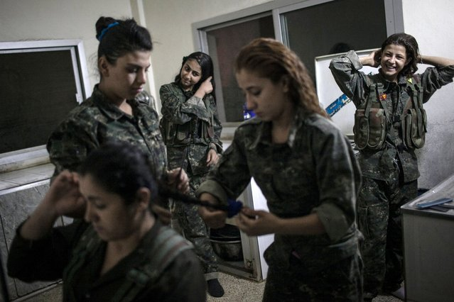 Young YPJ recruits Fix their hair at 4:30 AM before participating in training exercises and drills, near Derek City, Syria. The YPJ schedule is demanding and requires discipline – new soldiers in training get about 6 hours of sleep a night and wake up at 4 AM; their day consists of a full schedule of drills and classroom lessons. Before joining the YPJ many of the girls had never participated in physical activity or sports before. (Photo by Erin Trieb/NBC News)