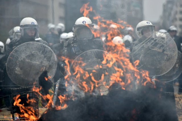 Police officers stand guard in front of a burning barricade as farmers and dairy farmers from all over Europe take part in a demonstration outside a European Union agricultural ministers' emergency meeting at the EU Council headquarters in Brussels, Belgium September 7, 2015. (Photo by Eric Vidal/Reuters)
