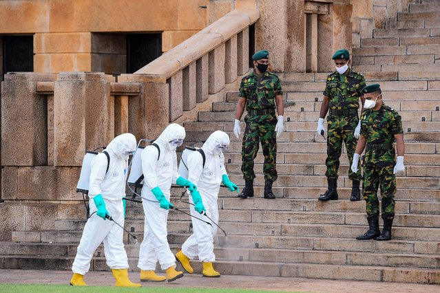 Special Task Force (STF) personnel (L) wearing protective gear spray disinfectant outside the Presidential Secretariat as security personnel stand guard during a government-imposed nationwide lockdown as a preventive measure against the COVID-19 coronavirus, in Colombo on April 10, 2020. (Photo by Ishara S. Kodikara/AFP Photo)