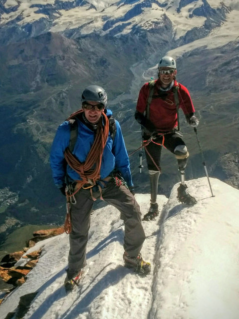 In this handout picture taken Thursday August 4, 2016 British quadruple amputee mountaineer Jamie Andrew,  right,  and  Steve James, who accompanied him,  stand on Matterhorn Mountain in Switzerland.  The  British mountaineer who climbed Switzerland's iconic Matterhorn says he is the first quadruple amputee to do so. Jamie Andrew lost his hands and feet to frostbite after becoming trapped in a snowstorm while mountaineering in France 17 years ago. (Courtesy of Jamie Andrew via AP Photo)