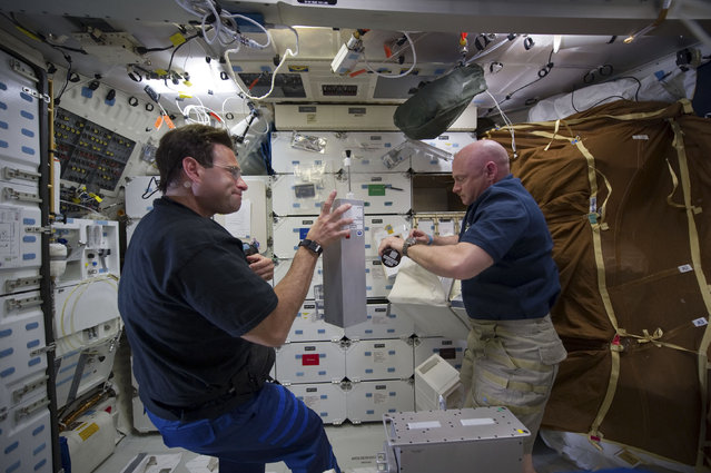 NASA astronauts Greg Chamitoff (L), mission specialist, and space shuttle Endeavour Commander Mark Kelly, work on the orbiter's middeck on May 17, 2011. (Photo by Reuters/NASA)