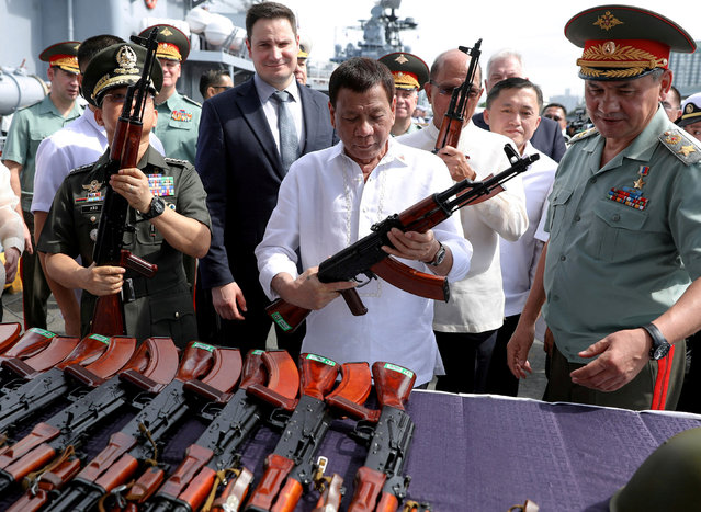This handout photograph released by the Presidential Photo Division (PPD) on October 25, 2017 shows Philippine President Rodrigo Duterte (L) inspecting Kalashnikov assault rifles with Russia' s Defence Minister Sergei Shoigu (R) during a handover ceremony at the Port of Manila Russia handed over thousands of assault rifles to Philippine President Rodrigo Duterte on October 25 as it celebrated its new partnership with a longtime US military ally in Asia. (Photo by Reuters/Malacanang Presidential Photo)