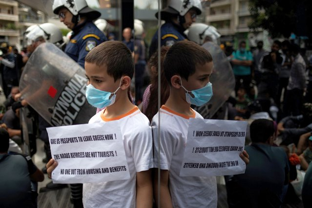 A boy wears a face mask as protection from the spread of the coronavirus disease (COVID-19) while refugees protest outside the UNHCR offices against a government decision that they should leave their accommodation provided through European Union and UNHCR funds by the end of May, in Athens, Greece, May 29, 2020. (Photo by Alkis Konstantinidis/Reuters)