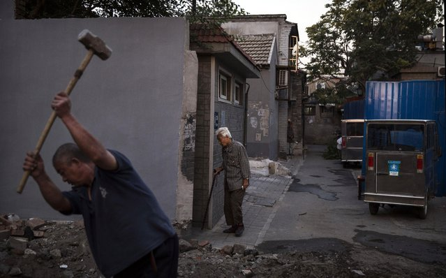 A Chinese worker uses a sledghammer as he breaks apart concrete from an old traditional Hutong or house, as a resident walks to a communal bathroom on September 18, 2014 in central Beijing, China. (Photo by Kevin Frayer/Getty Images)