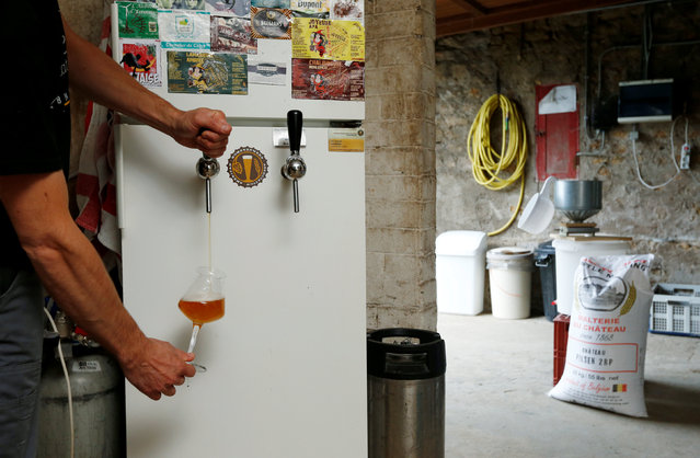 Axel Henrard, psychologist and President of the Belgian Homebrewers association, pours his own beer in a former barn of his house in Attert, Belgium, August 11, 2016. (Photo by Francois Lenoir/Reuters)