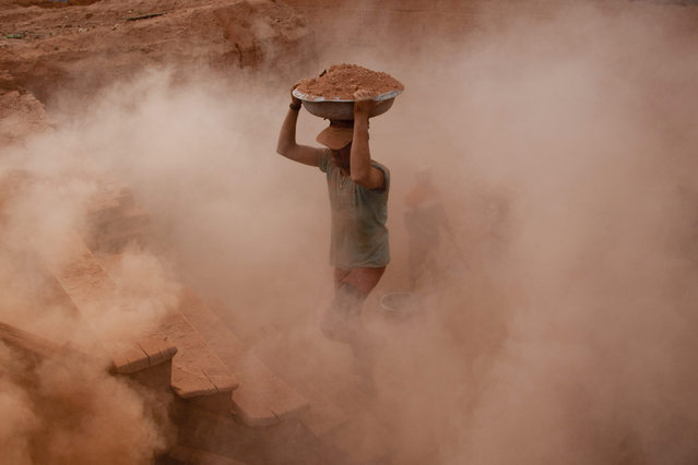 Indian laborers work at a brick kiln in Budgham area, southwest of Srinagar, Indian controlled Kashmir, Tuesday, September 8, 2015. Brick making is an unorganized industry, generally confined to rural and semi-urban areas and is one of the largest employment-generating industries in India. The laborers usually work in hard conditions for 12-14 hours a day to reach a target of 1,000 to 1,200 bricks a day, earning between US$ 100 to 140 a month. (Photo by Dar Yasin/AP Photo)