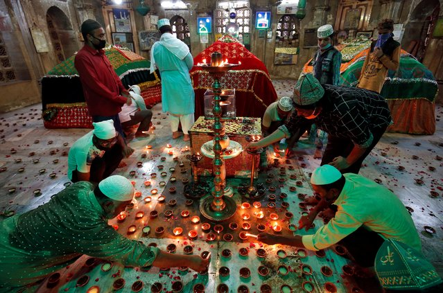 People light oil lamps inside the tomb of Ahmad Shah during a special prayer meeting for the victims of the coronavirus disease (COVID-19), amid the spread of the disease in Ahmedabad, India, June 30, 2020. (Photo by Amit Dave/Reuters)