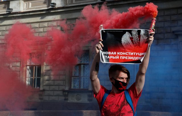 "An activist takes part in a protest against amendments to Russia's Constitution following the announcement of the results of the week-long vote on constitutional reforms, in central Saint Petersburg, Russia on July 2, 2020. The placard reads: ""The new constitution, the old president"". (Photo by Anton Vaganov/Reuters)"