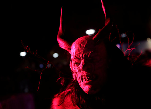 A man dressed as a devil attends a Krampus show, the traditional parade where people in costumes and masks perform an old ritual to disperse the ghosts of winter, in Schladming, Austria, November 25, 2017. (Photo by Leonhard Foeger/Reuters)