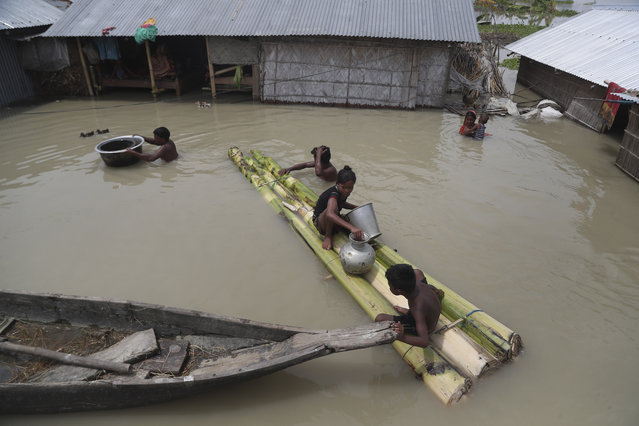 Flood affected villagers are seen near their partially submerged houses in Gagolmari village, Morigaon district, Assam, India, Tuesday, July 14, 2020. Hundreds of thousands of people have been affected by floodwaters and landslides following incessant rainfall in the region. (Photo by Anupam Nath/AP Photo)