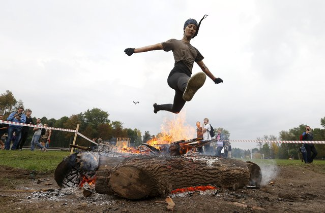 A woman jumps over the fire as she takes part in an extreme run competition in Zhodino, east of Minsk, September 26, 2015. (Photo by Vasily Fedosenko/Reuters)
