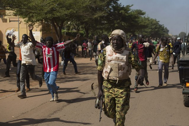A soldier runs from anti-government protesters as they take over the parliament building in Ouagadougou, capital of Burkina Faso, October 30, 2014. Thousands of protesters marched on Burkina Faso's presidential palace after burning the parliament building and ransacking state television offices on Thursday, forcing President Blaise Compaore to scrap a plan to extend his 27-year rule. (Photo by Joe Penney/Reuters)