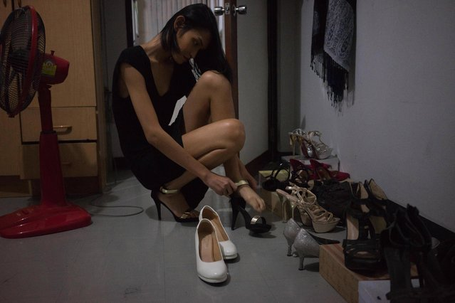 "Kritchaya ""Lolita"" Boonhor picks up high heels from her abundant collection in her room and puts on one of them before she goes out to have party, in Bangkok, Thailand, 28 November 2017. (Photo by Lola Levan/EPA/EFE)"