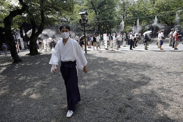 Visitors queue to enter Yasukuni Shrine Saturday, August 15, 2020, in Tokyo. Japan marked the 75th anniversary of the end of World War II. (Photo by Eugene Hoshiko/AP Photo)