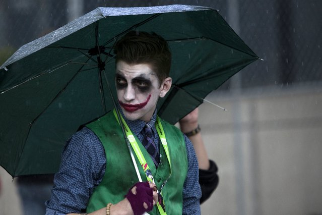 """A man dressed as """"The Joker"""" uses an umbrella as rain falls on day two of New York Comic Con in Manhattan, New York, October 9, 2015. (Photo by Andrew Kelly/Reuters)"""