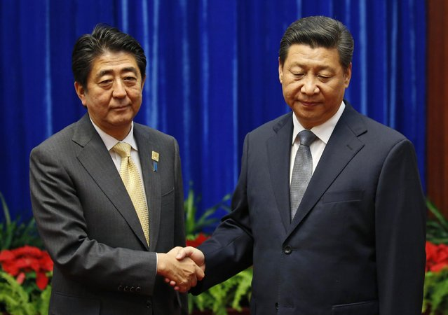 China's President Xi Jinping (R) shakes hands with Japan's Prime Minister Shinzo Abe during their meeting at the Great Hall of the People, on the sidelines of the Asia Pacific Economic Cooperation (APEC) meetings, in Beijing November 10, 2014. Xi and Abe held formal talks on Monday for the first time since the two leaders took office, a breakthrough in ending a two-year row between Asia's biggest economies over history and territory. (Photo by Kim Kyung-Hoon/Reuters)