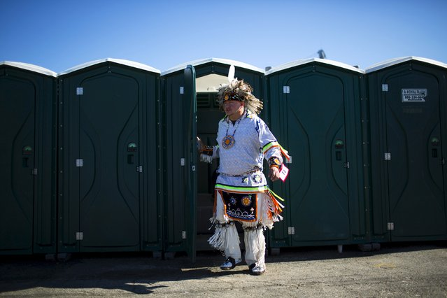 "A reveller exits a mobile toilet during a ""pow-wow"" celebrating the Indigenous Peoples' Day Festival in Randalls Island, New York, October 11, 2015. (Photo by Eduardo Munoz/Reuters)"
