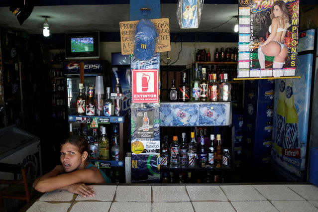A woman waits for customers inside a liquor store in Villa Rosa, near Porlamar, Venezuela September 16, 2016. (Photo by Marco Bello/Reuters)