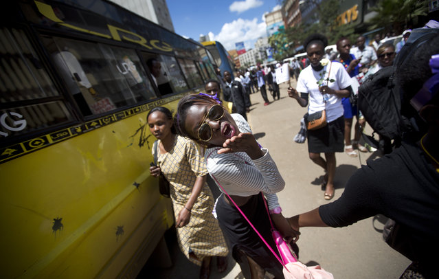 A Kenyan woman protesting with others for the right to wear whichever clothes they want, blows a kiss towards the camera, at a demonstration in downtown Nairobi, Kenya Monday, November 17, 2014. (Photo by Ben Curtis/AP Photo)