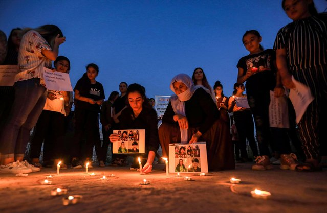 Iraqi Yazidis attend a candle-lit vigil in the Sharya area, some 15 kilometres from the northern city of Dohuk in the autonomous Iraqi Kurdistan region on August 3, 2020, marking the sixth anniversary of the Islamic State (IS) group's attack on the Yazidi community in the northwestern Sinjar district. (Photo by Safin Hamed/AFP Photo)