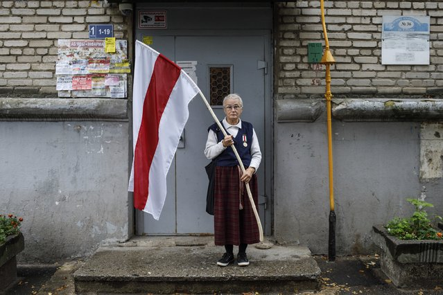Nina Bahinskaya, 73, poses for a photo holding an old Belarusian national flag at an entrance of her apartment building in Minsk, Belarus, Thursday, September 10, 2020. The 73-year-old former geologist has become one of the most recognizable faces of Belarus protests, fearlessly waving a huge opposition's red-and-white flag in front of riot police. (Photo by AP Photo/Stringer)