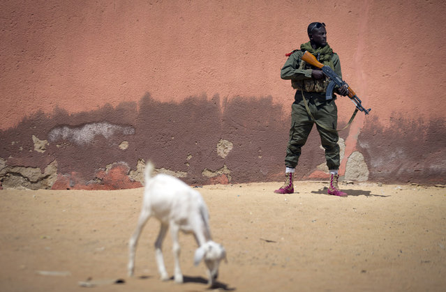 Malian army soldier Sekou Bolly, 30, holds an AK-47 assault rifle as he patrols in Gao, on February 25, 2013. (Photo by Joel Saget/AFP Photo/The Atlantic)