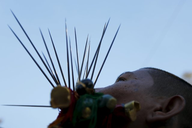 A devotee of the Chinese Jui Tui shrine walks with spikes pierced through his cheeks during a procession celebrating the annual vegetarian festival in Phuket, Thailand October 19, 2015. (Photo by Jorge Silva/Reuters)