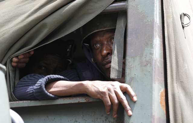 A riot police officer looks out peers from a truck before firing teargas to disperse the #OccupyHarambeeAve demonstration in Kenya's capital Nairobi November 25, 2014. (Photo by Thomas Mukoya/Reuters)