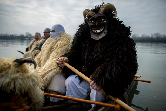 Men wearing sheepfur costumes with horns and masks prepare to paddle a boat across River Danube from an island to Mohacs, some 210 kms south of Budapest, to participate in the traditional carnival parade of the town 11 February 2018.The carnival parade of people dressed in similar costumes and frightening wooden masks, using various noisy wooden rattlers is traditionally held on the seventh weekend before Easter to drive away winter, and is a revival of a legend, which says the ethnic Croats crossed the river to ambush the Osmanli Turkish troops, who escaped in panic seeing the terrifying figures during the Turkish occupation of Hungary. (Photo by Tamas Soki/EPA/EFE)