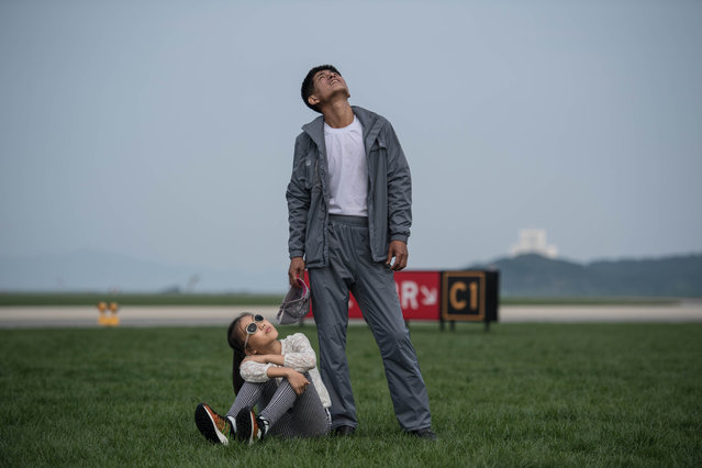 A man and child watch a aerial display during the second day of the Wonsan Friendship Air Festival in Wonsan on September 25, 2016. Just weeks after carrying out its fifth nuclear test, North Korea put on an unprecedented civilian and military air force display Saturday at the country's first ever public aviation show. (Photo by Ed Jones/AFP Photo)