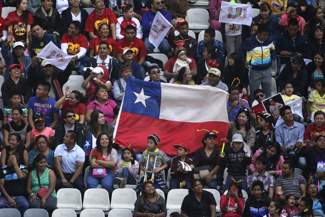 Chileans hold their national flag as they wait for the mass held in memory of the late screenwriter Roberto Gomez Bolanos to begin at the Azteca stadium in Mexico City November 30, 2014. (Photo by Tomas Bravo/Reuters)