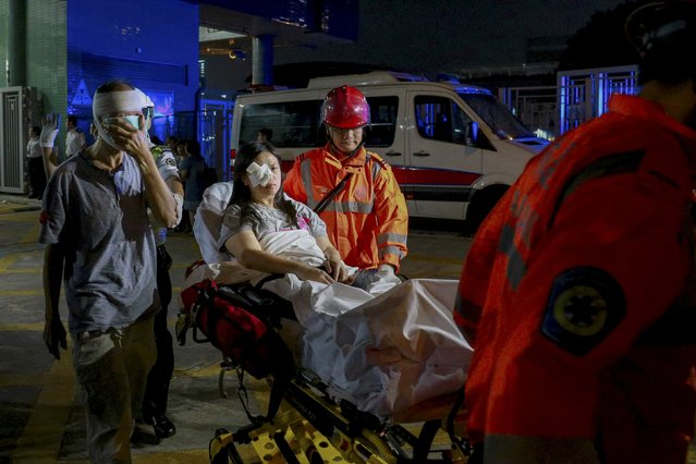 Injured ferry passengers are escorted by rescuers after getting onshore in Hong Kong, China October 25, 2015.  About 100 people were injured on Sunday when a ferry returning from Macau to Hong Kong collided with an unknown object, a police department official said. (Photo by Reuters/Stringer)