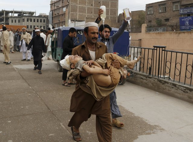 A man carries a boy, who was injured in an earthquake, at the Lady Reading hospital in Peshawar, Pakistan October 26, 2015. (Photo by Khuram Parvez/Reuters)