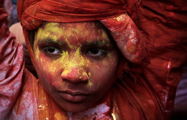 A young villager from Nandgaon is soaked in water and colored powder. (Photo by Manish Swarup/Associated Press)