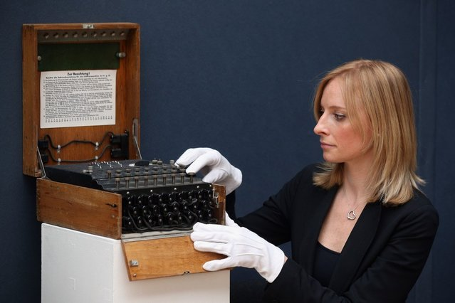 """An employee at Christie's auction house examines an Enigma cipher machine on March 27, 2013 in London, England. The Enigma machine is expected to fetch 60,000 GBP when it features in Christie's """"Travel, Science and Natural History"""" sale, which is to be held on April 24, 2013 in London.  (Photo by Oli Scarff)"""