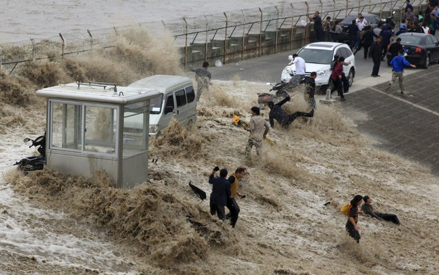 Visitors are hit by a wave caused by a tidal bore which surged past a barrier on the banks of Qiantang River, in Hangzhou, Zhejiang province, China, October 28, 2015. (Photo by Reuters/China Daily)