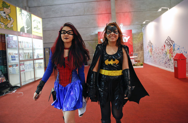 Women dressed as Spider woman and Bat woman cosplay at the Comic Con Experience fair in Sao Paulo, Brazil, Thursday, December 4, 2014. Sao Paulo hosted the international comic trade fair for the first time and plan to hold one every year. (Photo by Andre Penner/AP Photo)