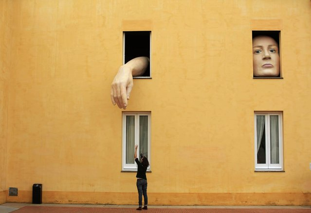"""A woman takes pictures of art installation """"Alice"""" by Spanish artist Cristina Lucas in the Andalusian Centre of Contemporary Art in the Andalusian capital of Seville, southern Spain April 10, 2013. (Photo by Marcelo del Pozo/Reuters)"""