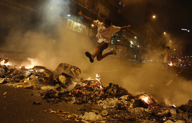A boy jumps over a barricade of burning garbage that supporters of opposition leader Henrique Capriles used to block a street, as they demonstrated for a recount of the votes in Sunday's election, in Caracas, April 15, 2013. Hundreds of protesters clashed with police in the Venezuelan capital on Monday after Capriles called for demonstrations to demand a recount of votes from Sunday's election to replace the late Hugo Chavez. (Photo by Tomas Bravo/Reuters)